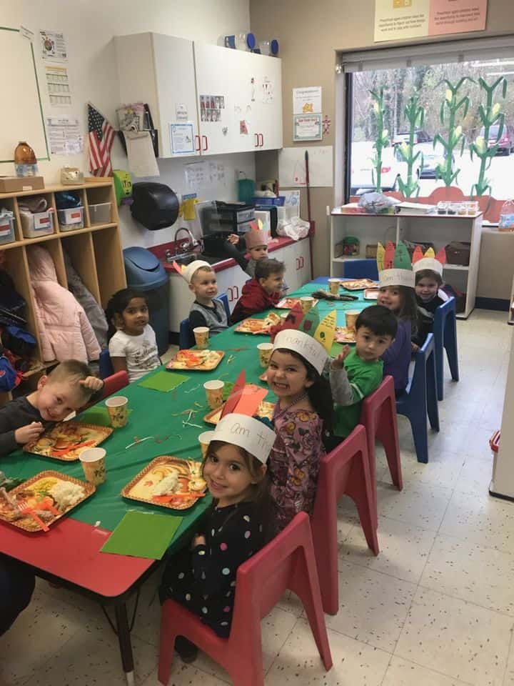 thanksgiving kindergarten class enjoying festive lunch with turkey hats